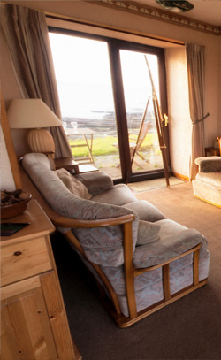 Enjoy the view of the highland coastline from the holiday cottage while relaxing in our fully furnished sitting room with dining area.